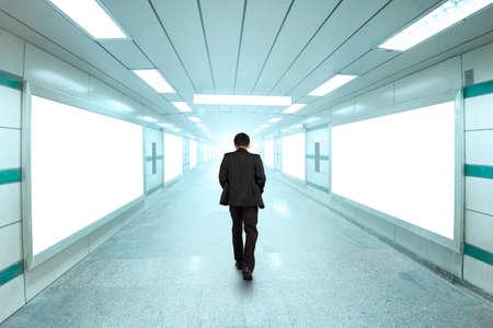 Foto de Rear view businessman walking through bright underpass, with blank billboard advertising wall. - Imagen libre de derechos