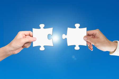 Foto de Man and woman two hands assembling jigsaw puzzle pieces, with blue background. Teamwork concept. - Imagen libre de derechos