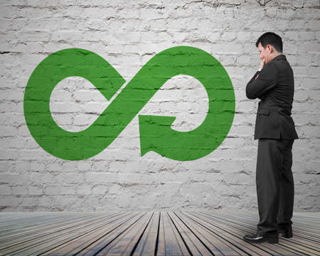 Green circular economy concept. Arrow infinity symbol on brick wall with man thinking.
