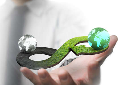 Photo pour Green circular economy concept. Man's hand showing arrow infinity symbol with grass texture and two globes of different colors. - image libre de droit