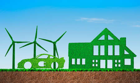 Foto de Green grass in shape of wind turbines, electric car and building, on blue sky and meadow soil cross section background, concept of ECO, renewable energy and circular economy. - Imagen libre de derechos