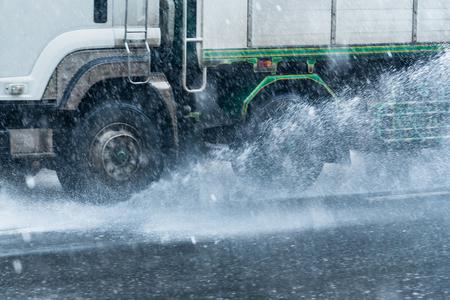 Rainwater spraying from motion truck wheels. city road during heavy rain.Thailand