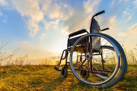 Foto de Empty wheelchair on the meadow at sunset. Miracle concept. Healed person raised and went away - Imagen libre de derechos