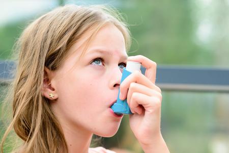 Foto de Girl having asthma using the asthma inhaler for being healthy - shallow depth of field - asthma allergy concept - Imagen libre de derechos