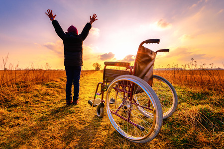 Foto de Miracle recovery: young girl gets up from wheelchair and raises hands up. Overjoyed young girl  standing up from a wheelchair outdoors. Shot in meadow. Recovery concept - Imagen libre de derechos
