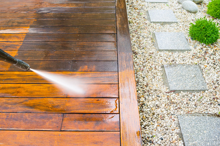 Foto per cleaning terrace with a power washer - high water pressure cleaner on wooden terrace surface - Immagine Royalty Free