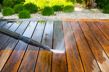 Foto de cleaning terrace with a power washer - high water pressure cleaner on wooden terrace surface - Imagen libre de derechos
