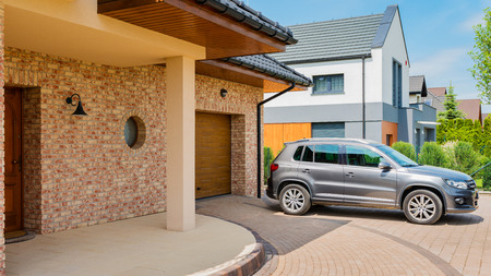 Foto de Residential house with silver suv car parked on driveway in front. Family house - perfect neighborhood concept - Imagen libre de derechos