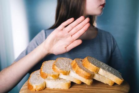 Foto de Gluten intolerance concept. Young girl refuses to eat white bread - shallow depth of field - selective focus on bread - Imagen libre de derechos