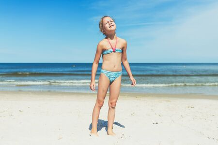 Photo pour Looking into the sun - a little girl on an empty sandy beach staring straight into the sun squinting - image libre de droit
