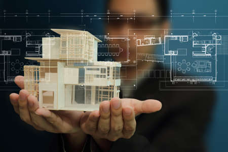 Foto per Businessman present house model and plan on touch screen - Immagine Royalty Free
