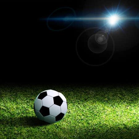 Soccer ball on grass against black background