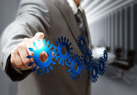 Foto de business man hand point cogs icons in board room - Imagen libre de derechos