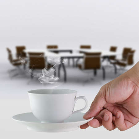 white coffee cup in hand business and meeting room background
