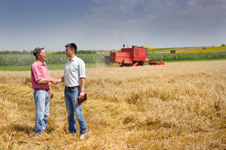 Photo pour Peasant and businessman shaking hands on wheat field - image libre de droit