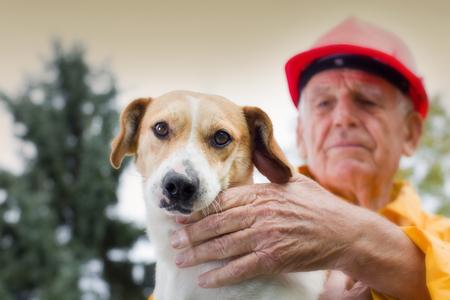 Foto de Old man rescuing dog from natural disaster - Imagen libre de derechos