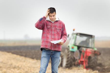 Foto für Worried young farmer standing on field and  looking at papers from bank, tractor in background - Lizenzfreies Bild