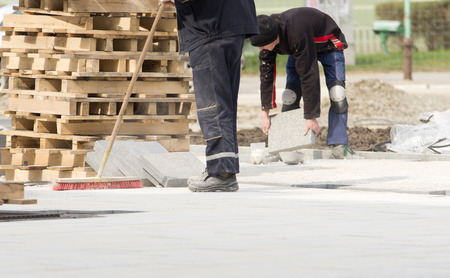 Photo for Construction worker in safety clothes cleaning building site after installing flagstones in sand - Royalty Free Image