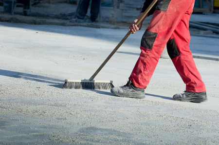 Photo pour Construction worker in safety shoes cleaning building site after paving work - image libre de droit