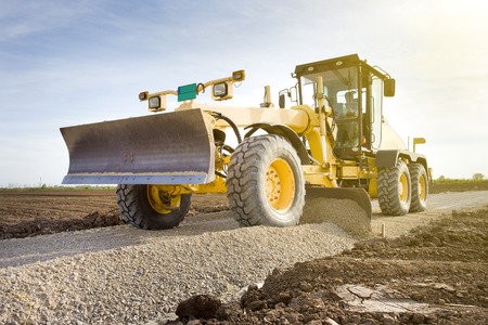Photo pour Grader leveling gravel on road construction site - image libre de droit