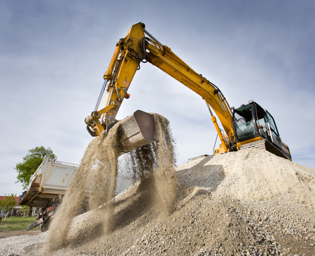 Photo pour Excavator standing on top of gravel hill and moving gravel with scoop - image libre de droit