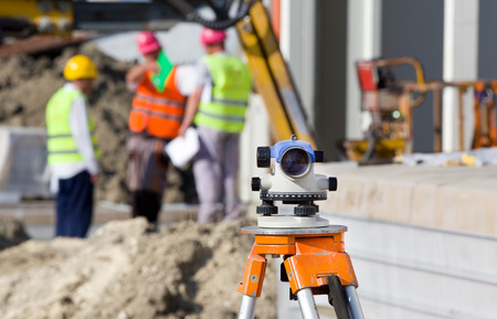 Photo pour Surveying measuring equipment level theodolite on tripod at construction site with workers in background - image libre de droit