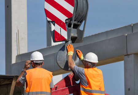 Foto de Construction worker navigating with concrete slab lifted by crane at building site - Imagen libre de derechos