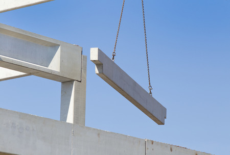 Photo pour Crane lifting concrete truss for installing in building skeleton - image libre de droit