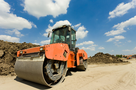 Photo pour Rusty roll compactor working on sand area at construction site - image libre de droit