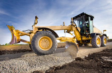 Foto per Grader leveling gravel on road construction site - Immagine Royalty Free