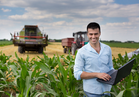 Foto für Young attractive farmer with laptop standing in corn field, tractor and combine harvester working in wheat field in background - Lizenzfreies Bild