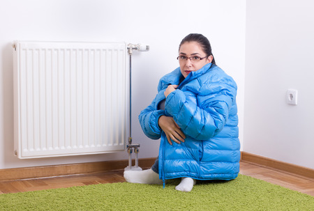 Foto de Young woman in blue winter jacket sitting next to cold radiator - Imagen libre de derechos