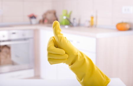 Foto de Conceptual image of home cleaning. Close up of human hand with yellow rubber glove showing ok sign with thumb up. Cleaned kitchen in background - Imagen libre de derechos
