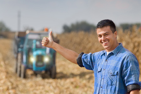 Foto für Young smiling farmer showing thumb up as ok sign on farmland. Tractor with trailer in background - Lizenzfreies Bild