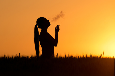 Photo for Silhouette of young woman smoking cigarette at sunset in wheat field - Royalty Free Image