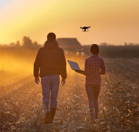 Foto de Farmer woman with laptop and landowner walking on field with drone flying above farmland at sunset - Imagen libre de derechos