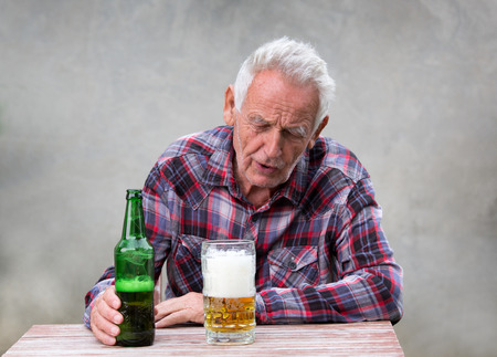 Foto de Senior drunk man sitting at table with beer bottle and mug in front of him - Imagen libre de derechos