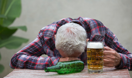 Foto de Senior drunk man sleeping at table with beer bottle and mug in front of him - Imagen libre de derechos