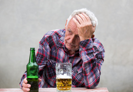 Foto de Senior man with hangover holding his head at table with beer bottle and mug in front of him - Imagen libre de derechos