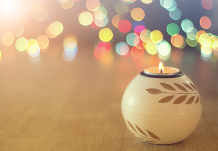 Photo pour Close up of candle burning on wooden table and colorful lights in background. Christmas and New year holiday concept - image libre de droit