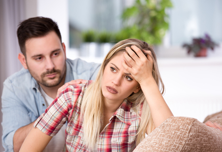 Photo for Young couple having problems in relationship, boyfriend feeling guilty. Sitting on sofa in living room - Royalty Free Image