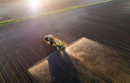 Photo pour Aerial image of tractor spraying soil and young crop in springtime in field - image libre de droit
