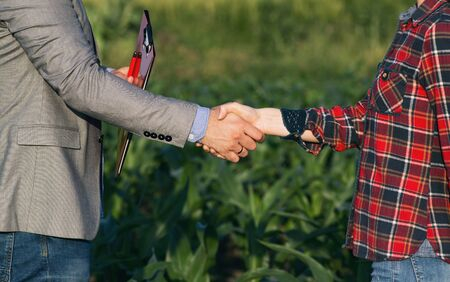 Photo pour Farmer woman shaking hands with business man with folder, in corn field - image libre de droit