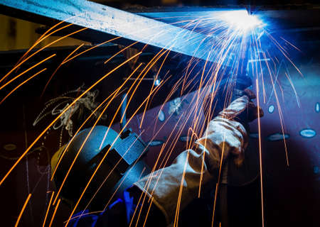 Photo for Worker with protective mask welding metal and sparks - Royalty Free Image