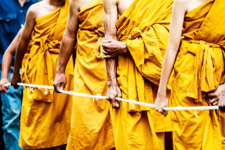 Monks stand in line to get offerings ,Thailand