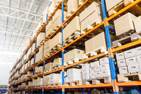 Foto de Rows of shelves with boxes in modern warehouse - Imagen libre de derechos