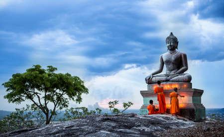 Foto de Yong buddhist monk fire candles to the Buddha - Imagen libre de derechos