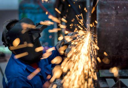 Foto de Electric wheel grinding on steel pipe in factory - Imagen libre de derechos