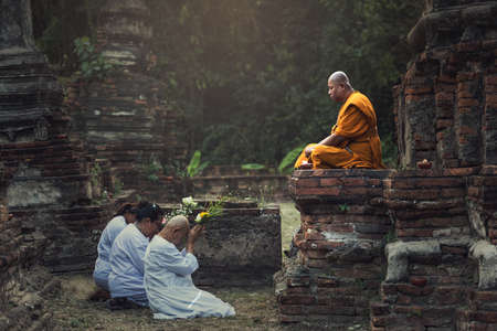 Photo for Ayutthaya, Thailand - February 22, 2016: People praying respect to monk on Ayutthaya. Roughly 95% of the Thai people are practitioners of Theravada Buddhism, the official religion of Thailand - Royalty Free Image