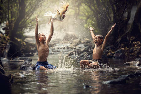 Photo for Boys playing with their duck in the creek - Royalty Free Image